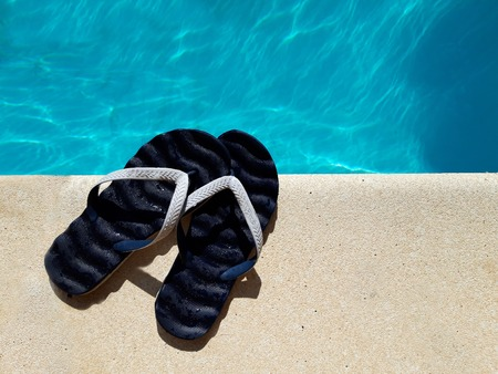 Photo for Summer background with slippers for the pool fuchsia colors near the pool - Royalty Free Image