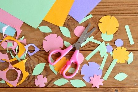 Photo for Paper flowers, paper sheets, scissors, paper scrap on a wooden table. Paper flower craft for kids. Children's art project - Royalty Free Image