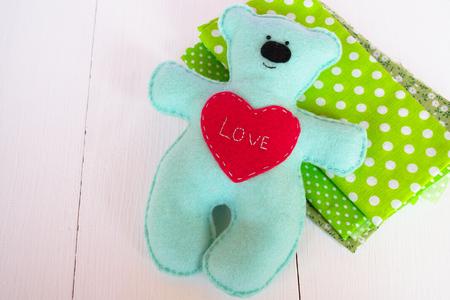 Foto de Handmade felt bear - felt on wooden background, hand-stitched toy, a craft out of felt - Imagen libre de derechos