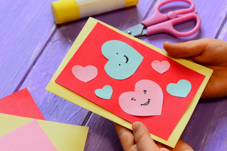 Photo for Child is holding a Valentines card in his hands. Child is showing a greeting card. Happy Valentines Day card. Easy paper crafts for kids concept. Closeup - Royalty Free Image