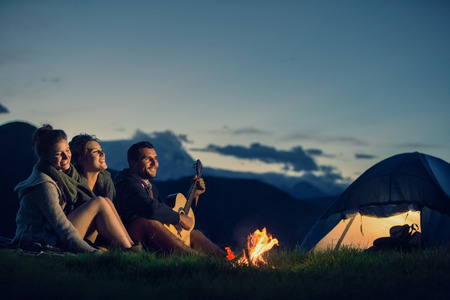 Photo for Three friends camping with fire on mountain at sunset - Royalty Free Image