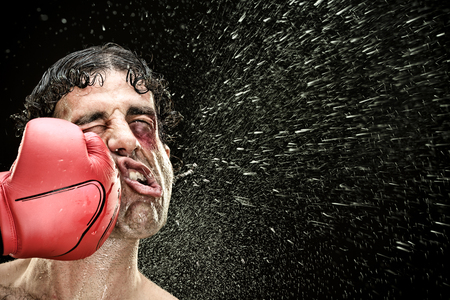 Photo for silly boxer man takes a punch in the face isolated on black.funny concept portrait - Royalty Free Image