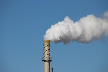 Foto de Steam comes out a chimney above a factory with white steam cloud on clear blue sky in Rotterdam - Imagen libre de derechos
