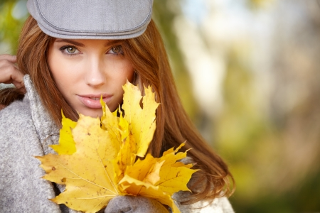happy fall woman smiling joyful and blissful holding autumn leaves outside in colorful fall forest