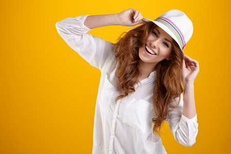 Photo for Young Woman with spring hat against yellow background  - Royalty Free Image
