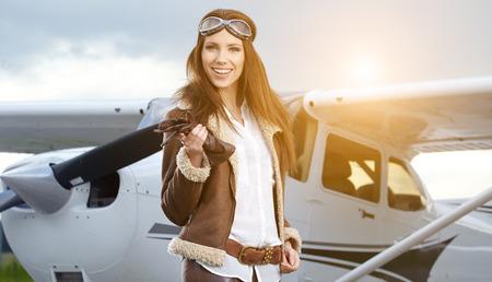 Photo pour Portrait of young beautiful woman pilot in front of airplane.  - image libre de droit