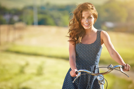 Photo pour Sexy woman with vintage bike in a country road. - image libre de droit
