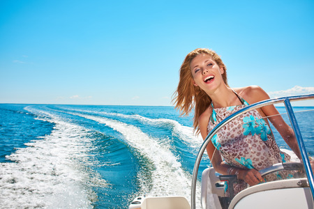 Photo for Summer vacation - young woman driving a motor boat - Royalty Free Image