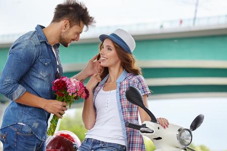 Photo pour Portrait of romantic man giving flowers to woman - image libre de droit