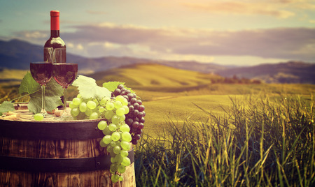 Photo pour Red wine bottle and wine glass on wodden barrel. Beautiful Tuscany background - image libre de droit