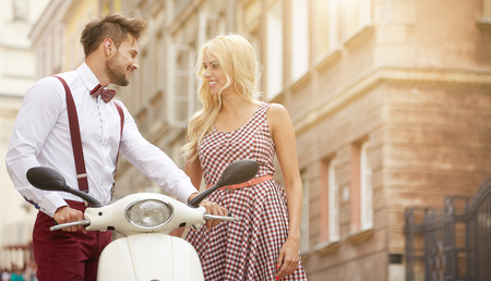 Photo for Love couple on the street with retro scooter - Royalty Free Image