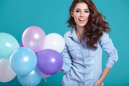 Photo for Happy young woman standing over blue wall and holding balloons. Pleasure. Dreams. Toned. - Royalty Free Image