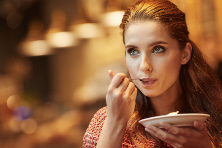 Photo for young beautiful woman eating a dessert - Royalty Free Image