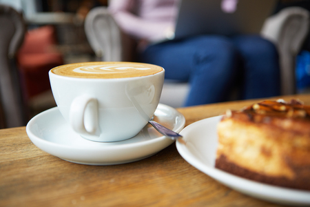Photo pour Two cups of coffee and cake on the table, latte art - image libre de droit