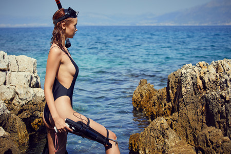 Foto per woman holding pink snorkel fins in black bikini on vacation - Immagine Royalty Free