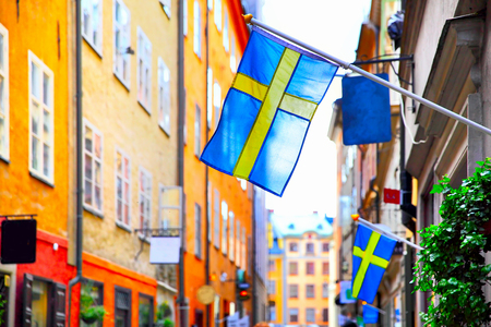 Photo pour Old street in Stockholm with swedish flags, Sweden. Shallow DOF, focus on the first flag - image libre de droit