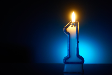 Foto de Number One - Burning birthday candle on blue background - Imagen libre de derechos
