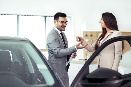 Photo for Salesperson selling cars at car dealership - Royalty Free Image