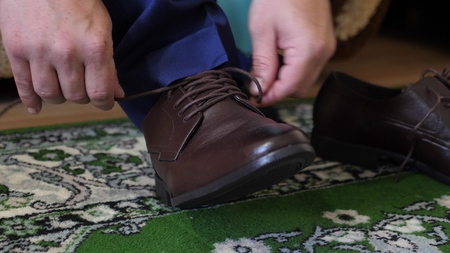 Photo for man tying shoelaces on brown shoes, a man in a white shirt and dark trousers. Businessman gets dressed in the morning to work. - Royalty Free Image