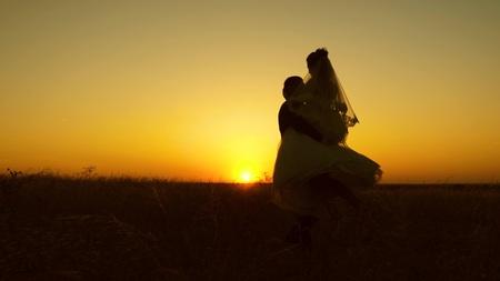 Foto de Young bride and groom circling on background of romantic red sunset. Honeymoon. The relationship between man and woman - Imagen libre de derechos