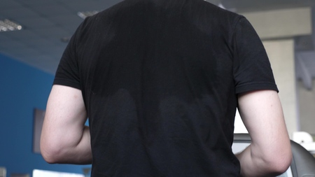 Foto per sweaty back men in T-shirt close-up. fitness club man engaged in walking. strengthening muscles of heart and legs by walking. cardio load. man trains on treadmill. walking in gym. weight loss in gym. - Immagine Royalty Free