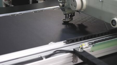 Photo for Robot sewing machine. computer controls the sewing machine. automatic sewing machine. automated machine embroider pattern on artificial leather. Robotics works in the tailoring production line. - Royalty Free Image