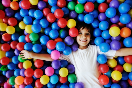 Foto de Little smiling boy playing lying in colorful balls park playground - Imagen libre de derechos