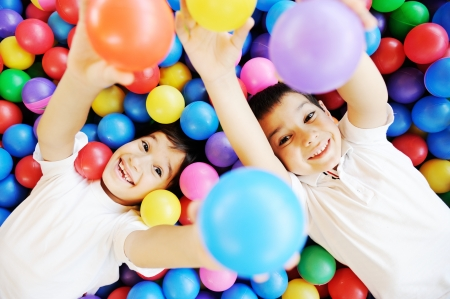 Photo pour Happy children playing together and having fun at kindergarten with colorful balls - image libre de droit