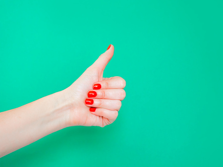 Photo for The Thumbs Up Sign. Like Hand Sign. Used when you want to demonstrate that you like something or that you approve of something, The ol thumbs up hand sign. Female hand with red manicure on fingernails holding hand in gesture of likeness giving thumb up on isolated turquoise green color background. - Royalty Free Image