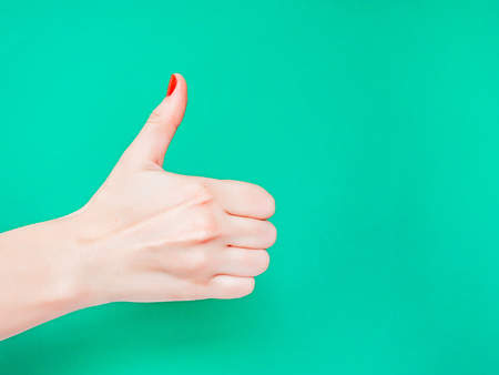 Photo for The Thumbs Up Sign. Like Hand Sign. Used when you want to demonstrate that you like something or that you approve of something, The ol thumbs up hand sign. Female hand with red manicure on fingernails holding hand in gesture of likeness giving thumb up on isolated turquoise green color background - Royalty Free Image