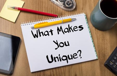 Foto de What Makes You Unique? - Note Pad With Text On Wooden Table - with office  tools - Imagen libre de derechos