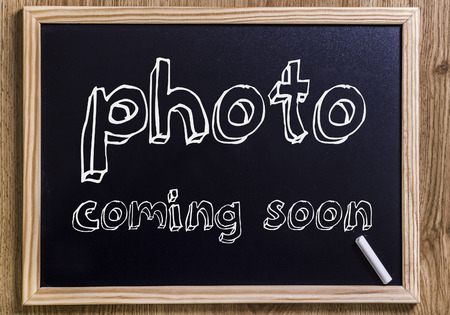 Foto de photo coming soon - New chalkboard with outlined text - on wood - Imagen libre de derechos