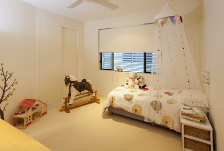 Little girl's bedroom with bed, rocking horse, toys and books