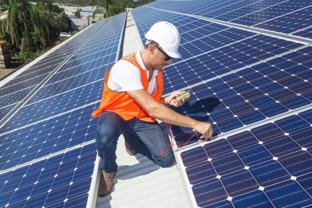 Photo pour Young technician checking solar panels on factory roof - image libre de droit