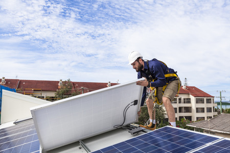 Photo pour Solar panel technician checking solar panel installation on roof - image libre de droit