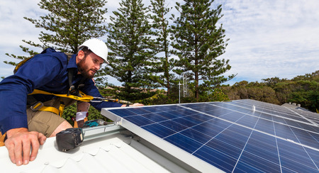 Photo pour Solar panel technician with drill installing solar panels on roof - image libre de droit