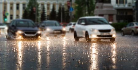 Heavy rain hitting a concrete sidewalk while cars drive by. Selective focus