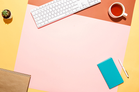 Photo pour Trendy home office workspace. Flat lay composition of keyboard, cactus, diary with pen and cup of tea on colorful desk. Pink, yellow, aquamarine and and brown colours. Blogger's home office. - image libre de droit