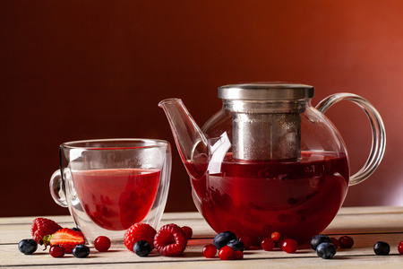 Foto de Mint tea with forest berries in a cup of double glass and a glass teapot on a wooden table, on a red background. - Imagen libre de derechos