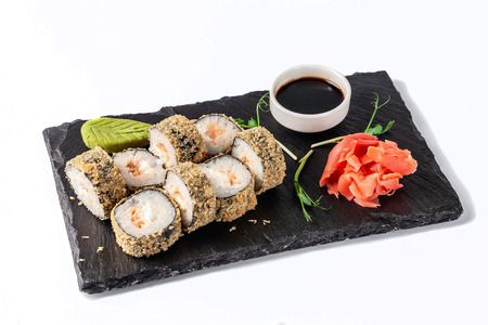Photo pour Concept of Japanese cuisine. Deep fried roll with salmon and mayonnaise in Panko bread crumbs. Near soy sauce, ginger and wasabi. Modern serving dishes in the restaurant on a black slate blackboard.  - image libre de droit