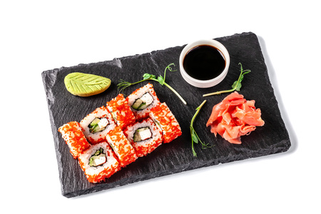 Photo pour Concept of Japanese cuisine. Roll with crab sticks, cucumber and celery, with red caviar. Near soy sauce, ginger and wasabi. Modern serving dishes in the restaurant on a black slate blackboard. - image libre de droit