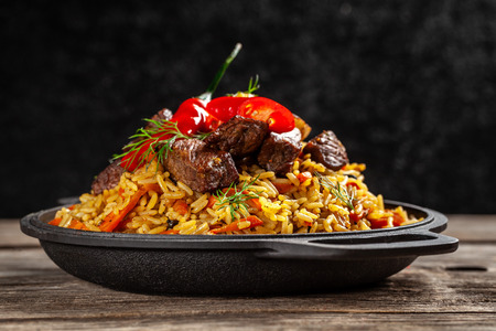 Photo pour The concept of oriental cuisine. National Uzbek pilaf with meat in a cast-iron skillet, on a wooden table. background image. top view, copy space, flat lay - image libre de droit