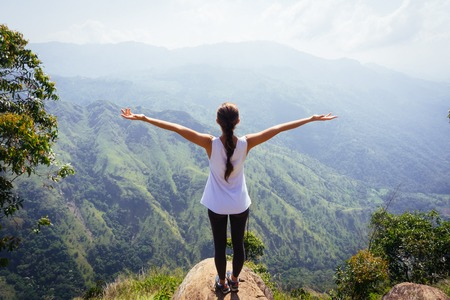 Photo pour Sporty woman standing with raised arms on the top oh hill - image libre de droit