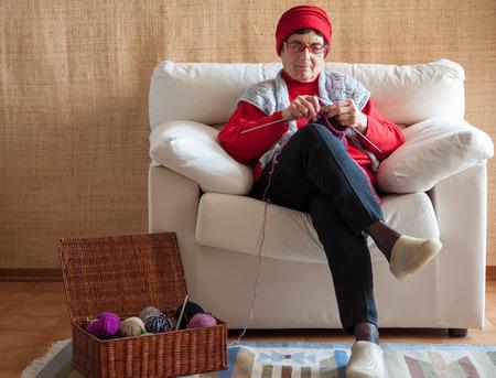 Foto de old woman knitting, sitting in her armchair - Imagen libre de derechos