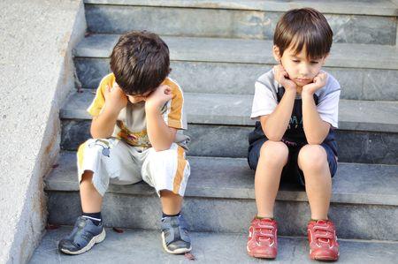 Two sad children on steps