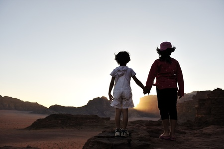 Waiting for the sunset in desert, brother and sister together visiting Africa. Boy and girl