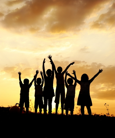 Photo for Silhouette, group of happy children playing on meadow, sunset, summertime - Royalty Free Image