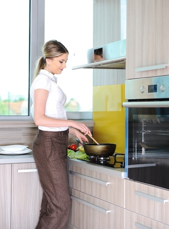 Young beautiful blonde woman cooking in kitchen