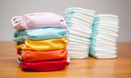 Foto de Stacks of disposable diapers and modern cloth diapers together - Imagen libre de derechos