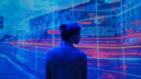 Photo pour Woman looking around and watching video presentation on large display wall at futuristic technology exhibition - image libre de droit